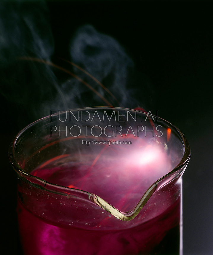 POTASSIUM REACTS EXPLOSIVELY WITH WATER<br /> Elemental Potassium in Beaker of Water.<br /> An exothermic displacement reaction between elemental Potassium and water producing aqueous Potassium Hydroxide and Hydrogen gas. Phenolphthalein indicator in the water turns pink as the solution becomes basic with the formation of Potassium Hydroxide.