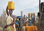 A woman carries water from a communal water point inside a camp for internally displaced families located inside a United Nations base in Juba, South Sudan. The crowded camp holds Nuer families who took refuge there in December 2013 after a political dispute within the country's ruling party quickly fractured the young nation along ethnic and tribal lines. The ACT Alliance is providing a variety of services, including fresh water and sanitation services, to the more than 20,000 people living in the camp.