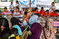 Pregnant women and lactating mothers register to receive SPRINT-IPPF dignity kits and other reproductive health (RH) information at a RH Medical Mission in the Taluksangay Barangay Hall, Zamboanga, Mindanao, The Philippines on November 5, 2013. These Internally Displaced People (IDP) had taken refuge in this Barangay (neighbourhood) after surviving the 3 week long attack by MNLF rebels. Photo by Suzanne Lee for SPRINT-IPPF