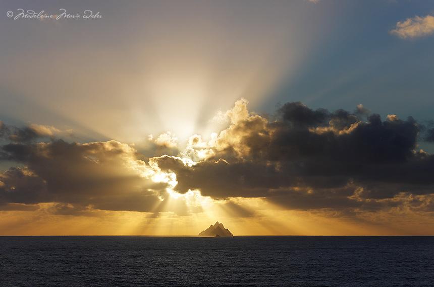 Sunset beams behind Skelligs, County Kerry, Ireland