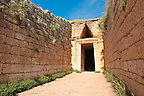 """Entrance to the Treasury of Atreus is an impressive """"tholos"""" beehive shaped tomb on the Panagitsa Hill at Mycenae. The entrance has the typical square 2 upright jams covered with a lintel that weigts around 100 tons. Above the door is a trangular """"False"""" or corbel arch.  Mycenae UNESCO World Heritage  Archaeological Site, Peloponnese, Greece"""