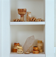 A collection of bangles and ancient Israeli goblets is displayed on shelves in the bedroom