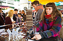 London, UK. 25.10.2014. Young woman serving natural licorice on a sweet stall at Borough Market, Southwark. Photograph © Jane Hobson.