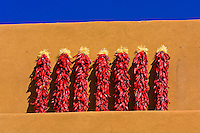 Ristras (decorative arrangements of dried red chile pepper pods) hang from the side of an adobe building, Inn on the Alameda (hotel), Santa Fe, New Mexico