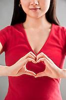 Asian woman making heart sign