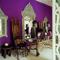 A collection of tribal art is displayed against a bright purple wall hung with Indian mirrors inlaid with mother of pearl in a loggia off the central courtyard