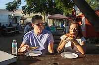 Young couple enjoys food at an Eastside food trailer park; East Austin's East 6th Street offers the Best Food Trucks Austin.