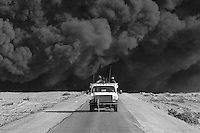 Private security operators from the British company ArmorGroup escort a supply convoy past a burning truck on the road from Baghdad to Al Asad air base, near Iraq's border with Syria on October 22, 2006. The coalition forces and civilian administration in Iraq depend heavily on the controversial presence of thousands of private security personnel in their reconstruction efforts and military operations.