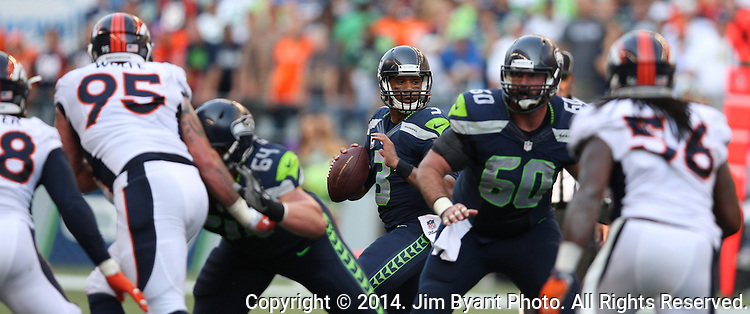 Seattle Seahawks quarter Russell Wilson (3) looks to pass against the Denver Broncos as center Max Unger provides pass blocking protection at CenturyLink Field in Seattle, Washington on September 21, 2014.  Wilson completed 24 of 34 passes for 258 yards, two touchdowns and one interception in the 26-20 overtime win against the Broncos.  ©2014. Jim Bryant Photo. All rights Reserved.
