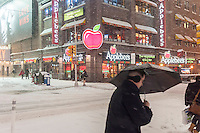 "An Applebee's casual dining restaurant in Times Square in New York during a snow storm on Tuesday evening, January 21, 2014. The official snowfall in Central Park was 11 inches (28 centimeters) which was a record for the day.  Brutal ""Polar Express"" temperatures in the single digits accompanied the snow with the arctic temperatures expected to last several days.  (© Richard B. Levine)"