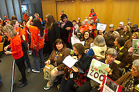 The Seattle City Council chamber was packed on Monday, March 9th, with a flood of people divided over the fate of Woodland Park Zoo elephants, Chai and Bamboo.  Supporters who want the elephants to retire to a sanctuary wore orange tee shirts while those who were in favor of them staying within the zoo system wore brown. (photo © Karen Ducey Photography)