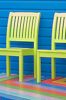 A pair of lime green chairs has been placed against the blue clapboard exterior of the beach hut and the surrounding terrace has been painted in multi-coloured stripes