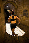 Woman jogging through an alley.