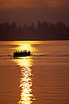 Eight man crew on Union Bay, silhouetted at sunrise with oars in water creating wake, reflections, Seattle, Washington USA