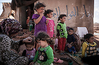 In this Sunday, Sep. 22, 2013 photo, Syrian internal displaced families sit outside an abandoned structure in a no man's land where they have taken shelter after have fled from Kafr Nabudah village, their homeland turned into a battlefield where clashes between troops loyal to president Bashar Al-Assad and opposition fighters have broken out as many opposition armed groups launched a coordinated attack over the Syrian army positions in the Idlib province countryside, Syria. (Photo/AP).