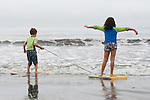 Stinson Beach CA  Siblings, age six and eight, playing together with boogie board on beach vacation MR
