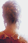 Headshot of young woman seen from behind with hair in plait