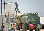 A man adds water to a tank in the Zaatari refugee camp near Mafraq, Jordan. Established in 2012 in a water-scarce region as Syrian refugees poured across the border, the camp held more than 80,000 refugees by 2015, and was rapidly evolving into a permanent settlement, with growing complaints about insufficient water for the residents. The ACT Alliance provides a variety of services to refugees living in the camp.