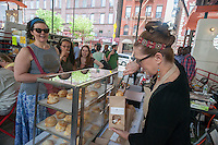 Annie Etheridge of Field & Clover sells her buttermilk biscuits at the kick-off of the annual Vendy Plaza at  La Marqueta in the East harlem neighborhood of New York on Sunday, May 24, 2015. The plaza area, La Marqueta Retoña, hosts a weekly vendors market drawing on food entrepreneurs from the streets around the city. (© Richard B. Levine)