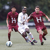 Boston College midfielder Derrick Boateng (10) dribbles as Harvard University defender Ross Friedman (4) defends.Boston College (white) defeated Harvard University (crimson), 3-2, at Newton Campus Field, on October 22, 2013.