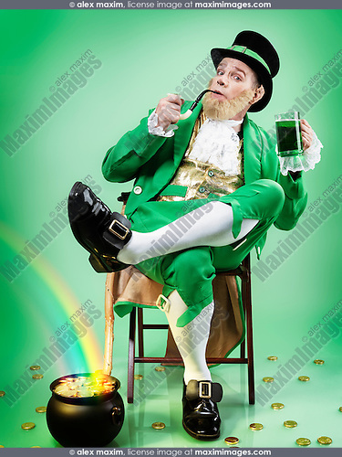 Leprechaun in green clothes holding a smoking pipe and a mug of green beer with a rainbow coming from a pot full of gold. Conceptual St. Patrick's holiday portrait. Isolated on white background.