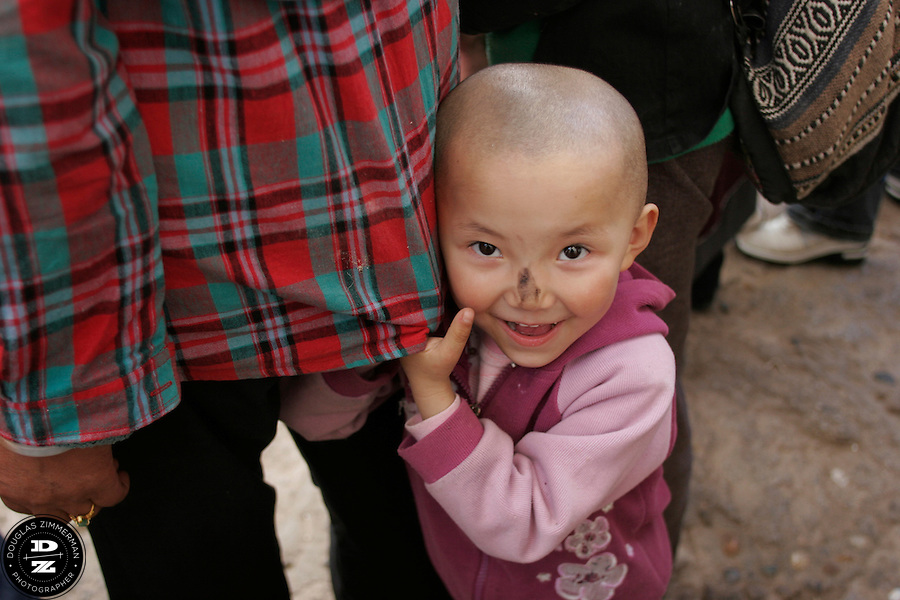 A young Tibetan child smiles while visiting the Sera Monastery outside Lhasa, Tibet.  Photograph by Douglas ZImmerman