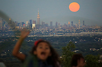 A girl reacts as the Blue moon rises next to the Empire State Building and middle Manhattan while it is seen from New Jersey.  07/31/2015. Eduardo MunozAlvarez/VIEWpress