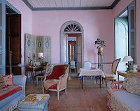 This living room is furnished with a variety of antiques and decorated a soft pink and blue
