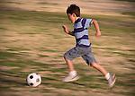 Boy runs after soccer ball - with motion blur