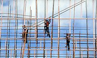 September 12th 1996-HONG KONG-Construction workers erect a bamboo scaffolding in from of a building in Central Hong Kong.  White clouds and blue sky are reflected in the buildings reflective facade.  Photo By Daniel J. Groshong/Tayo  Photo Group