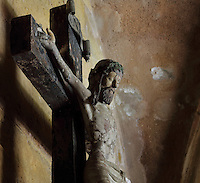 Sculpture of Christ on the cross, in the nave of the Old Cathedral of Coimbra, or Se Velha de Coimbra, a 12th century Romanesque Roman Catholic cathedral in Coimbra, Portugal. The cathedral was designed by Master Robert, a French architect, with the works overseen by Master Bernard and Master Soeiro. It was reworked in the 16th century, with the addition of tiled decoration, a portal and Renaissance chapel. The city of Coimbra dates back to Roman times and was the capital of Portugal from 1131 to 1255. Its historic buildings are listed as a UNESCO World Heritage Site. Picture by Manuel Cohen