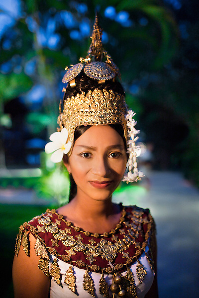A young Cambodian Apsara dancer walks on pathway at dusk at La Residence d'Angkor, Siem Reap, Cambodia. An Apsara dancer is a classical Khmer dancer.