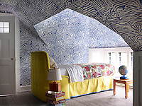 The walls of one of the guest bedrooms are clad in characteristically bold wallpaper with contrasting coloured furnishings