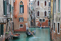 Gondolas on a narrow canal between buildings, Venice, Italy. Many of the houses and palazzos fronting the canals are in Venetian Gothic style, a style originating in the 14th century and combining Gothic lancet arches with Byzantine and Moorish influences. The city of Venice is an archipelago of 117 small islands separated by canals and linked by bridges, in the Venetian Lagoon. The historical centre of Venice is listed as a UNESCO World Heritage Site. Picture by Manuel Cohen