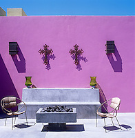 On the patio two antique metal crucifixes hang on the pink-painted wall above a concrete banquette