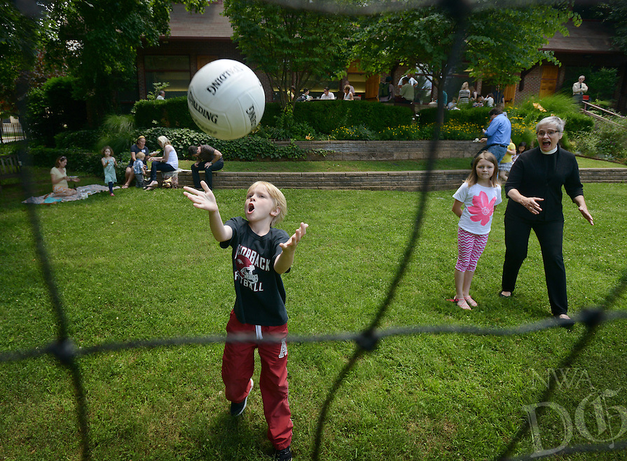 NWA Democrat-Gazette/BEN GOFF @NWABENGOFF<br /> Miller Rawn, 7, catches the ball while playing a game of Newcomb ball with London West, 10, and assistant rector Suzanne Stoner on Sunday June 5, 2016 during a parish picnic after service at St. Paul's Episcopal Church in Fayetteville.