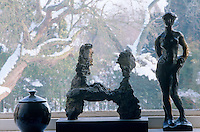 On a window sill of the living room three figures in bronze are outlined against the wintry landscape outside