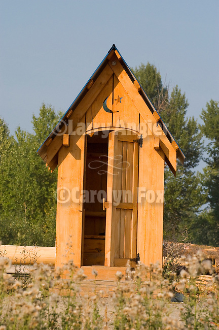 Wooden outhouse with crescent moon and star at log cabin manufacturing site near Price George, British Columbia