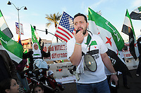 Mesa, Arizona. February 23, 2012 - As Republican candidates debated in the Mesa Arts Center, protesters including undocumented students, tea partiers, occupy movement members and Syrian president opponents, shouted slogans and held up signs and placards outside. In this photograph, Jehad Sibai, a member of an Arizona-based movement opposing Syrian president Bashar al-Assad politics, demonstrates outside the Presidential Republican debate. Sibai is a native of Syria and resident of the United States. Photo by Eduardo Barraza © 2012