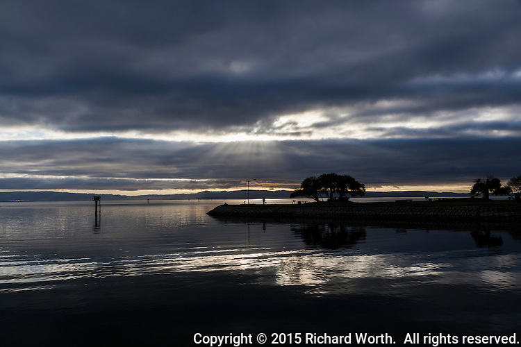 Shafts of sunlight shine onto San Francisco Bay. seen from the San Leandro Marina on a winter afternoon.