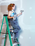 Portrait of a woman construction worker with a trowel and putty knife patching up drywall standing on a ladder