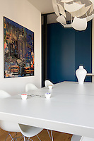The dining area is furnished with an Italian white lacquered aluminium table surrounded by Eames armchairs