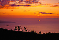 The sun sinks below the horizon to the right of the island of Kahoolawe and the smaller Molokini, which is a popular snorkeling destination. This view is at a 2,500-ft. elevation above the South Shore of Maui in upcountry Ulupalakua.