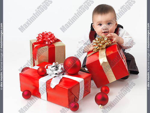 Happy six month old baby boy opening Christmas presents. Isolated on white background.