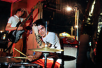 "Joel Shaeffer, left, and Pete Hansen wipe the sweat from their brows after playing with their band, Peace By Punching, at Café Berlin. ""It's an exhilarating feeling, beating everything out of me on the drums,"" says Hansen. With a strict D.I.Y. ""do-it-yourself"" ethic, Hansen organizes concerts at alternative venues with others in a burgeoning community of young artists in Columbia, Missouri. ""Putting on a show ourselves gives us incentive to play harder, and the power to make it what we want to make it."""