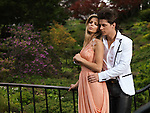 Young romantic couple standing on a bridge in a park. Springtime scenic.