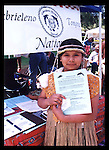 Gabrieleno/Tongva girl in traditional regalia hands out fliers about the Gabrieleno/Tongva people at the CSULB PowWow, Long Beach, CA