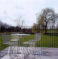 A set of wire mesh garden chairs and a table look out onto the river bank from the decked terrace