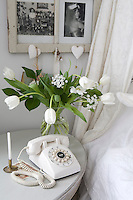Detail of a vase of white tulips and an old-fashioned white telephone on the bedside table