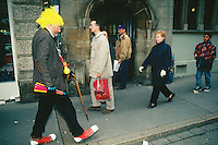 Switzerland. Basel. Fasnacht Carnival. A man with a yellow wig, a plastic trumpet, a comforter, a pair of clown's shoes and a stick walks in the street on the early morning.  © 1997 Didier Ruef